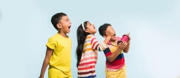 3 crianças indianas que voam o papagaio, uma que guarda spindal ou chakri imagem de stock royalty free