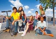 Crianças internacionais que sentam-se em cadeiras com 'trotinette' Imagens de Stock