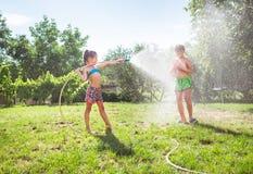 Crianças irmão e irmã, jogando com a mangueira molhando na tarde quente do verão imagem de stock
