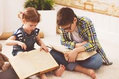 Crianças irmão e irmã, menino e menina lendo um livro foto de stock
