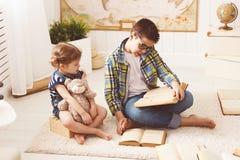 Crianças irmão e irmã, menino e menina lendo um livro fotos de stock