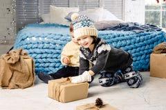 Crianças irmão e irmã que sentam-se no assoalho no quarto perto da cama que a menina está esticando à caixa com um presente no fu fotografia de stock
