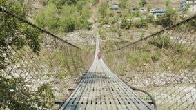 Crianças locais corridas e jogo na ponte de suspensão sobre o rio em Nepal video estoque