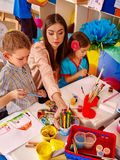 Crianças menina e menino com pintura da escova na escola primária Foto de Stock