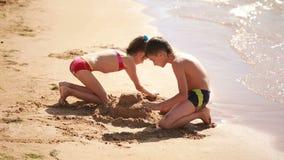 Crianças menino e menina que jogam com a areia na praia construa um castelo da areia video estoque