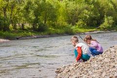 Crianças menino e menina que jogam perto do rio imagens de stock royalty free