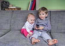 Crianças muito pequenas que olham a televisão Fotografia de Stock Royalty Free