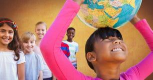 Crianças multinacionais e multiculturais que guardam o globo do mundo com fundo do ouro foto de stock