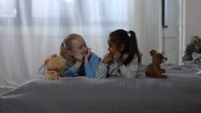 Crianças multirraciais alegres que têm o divertimento na cama video estoque