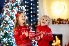 Crianças na árvore de Natal As crianças bebem o cacau quente fotos de stock