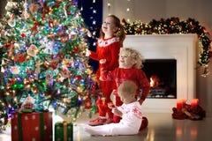 Crianças na árvore de Natal Crianças na chaminé na véspera do Xmas Fotografia de Stock