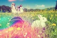 Crianças na caça do ovo da páscoa com coelho imagens de stock royalty free