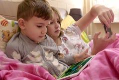 Crianças na cama que joga com dispositivos imagem de stock royalty free