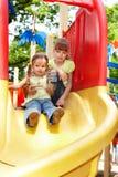 Crianças na corrediça ao ar livre no parque. Fotografia de Stock Royalty Free