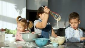Crianças na cozinha A menina agita a massa e olha-a fluir da corola Movimento lento vídeos de arquivo