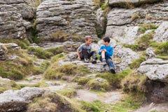 Crianças na natureza, no assento ou nas rochas Imagem de Stock Royalty Free