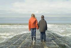 Crianças na praia, negligenciando o mar imagens de stock