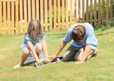 Crianças na roupa que joga com sistema de extinção de incêndios Imagem de Stock Royalty Free