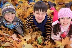 Crianças nas folhas de outono Fotografia de Stock