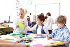 Crianças nas imagens da pintura da sala de aula durante classes de arte foto de stock