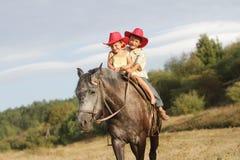 Crianças no cavalo de equitação do chapéu de cowboy ao ar livre imagens de stock royalty free