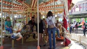 Crianças no passeio do divertimento do carrossel do carrossel vídeos de arquivo
