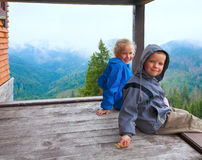 Crianças no patamar de madeira da casa de campo da montanha Imagens de Stock