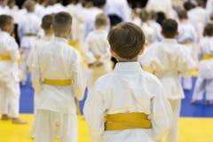 Crianças no quimono que senta-se no tatami no seminário das artes marciais imagens de stock