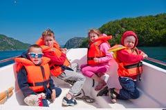 Crianças nos colete salva-vidas em um barco fotografia de stock