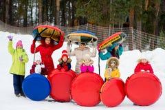 Crianças nos tubos da neve para baixo no dia de inverno Fotos de Stock