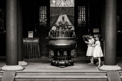 Crianças novas da geração que rezam para a boa sorte no templo chinês fotos de stock royalty free