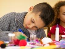 Crianças novas da raça misturada que fazem artesanatos Fotografia de Stock Royalty Free