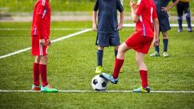 Crianças novas dos meninos nos uniformes que jogam o futebol do futebol da juventude Imagens de Stock Royalty Free