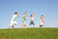 Crianças novas que funcionam através do campo Fotos de Stock Royalty Free