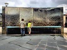 Crianças pela característica da água Fotografia de Stock Royalty Free