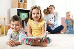 Crianças pequenas bonitos com livro dentro Aprendizagem e jogo foto de stock royalty free