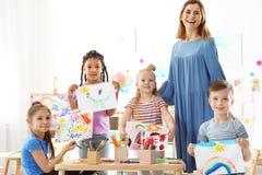 Crianças pequenas bonitos com o professor que mostra suas pinturas imagens de stock