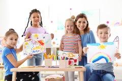 Crianças pequenas bonitos com o professor que mostra suas pinturas na lição imagem de stock