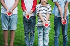 Crianças pequenas bonitos que guardam corações vermelhos ao estar na grama verde imagem de stock royalty free