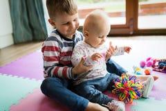 Crianças pequenas bonitos que jogam ao sentar-se no tapete fotos de stock royalty free
