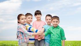 Crianças pequenas felizes com mãos na parte superior Fotografia de Stock Royalty Free