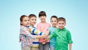 Crianças pequenas felizes com mãos na parte superior sobre o azul Imagens de Stock Royalty Free