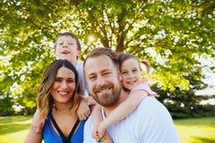Crianças pequenas felizes que abraçam seus pais Foto de Stock Royalty Free