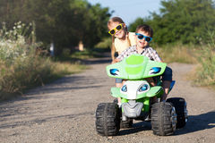 Crianças pequenas felizes que jogam na estrada no tempo do dia Imagem de Stock