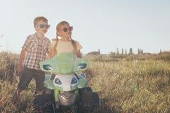 Crianças pequenas felizes que jogam na estrada no tempo do dia Imagem de Stock Royalty Free