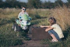 Crianças pequenas felizes que jogam na estrada no tempo do dia Fotos de Stock Royalty Free