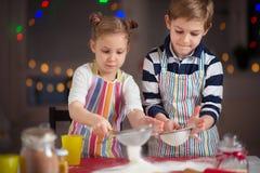 Crianças pequenas felizes que preparam cookies do Natal Fotos de Stock Royalty Free