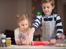 Crianças pequenas felizes que preparam cookies do Natal Foto de Stock