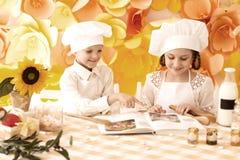 Crianças pequenas felizes sob a forma de um cozinheiro chefe para preparar delicioso Fotografia de Stock Royalty Free