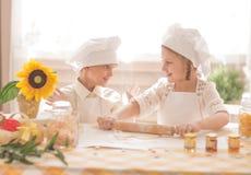 Crianças pequenas felizes sob a forma de um cozinheiro chefe para preparar delicioso Fotos de Stock Royalty Free